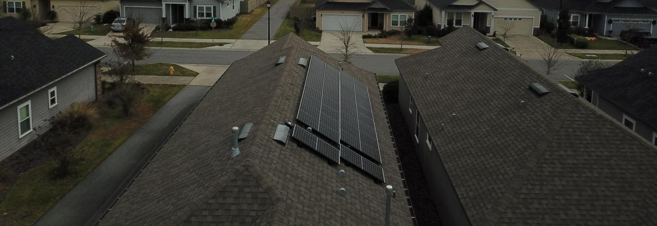 View of a roof in a neighborhood with black solar panels